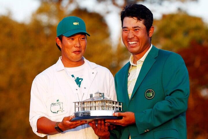 アジア人初の快挙を成し遂げグリーンジャケットを着る松山(右)と、それを支えた早藤キャディ(左)。(C)Getty Images